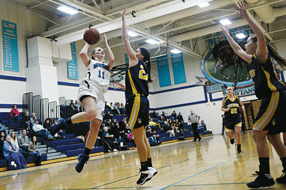 SEAN PROCTOR | sproctor@mdn.netMeridian's Madi Cassiday takes a shot against Roscommon's Lauren Shores Thursday night during their game at Meridian High School. Photo: Sean Proctor/Midland  Daily News
