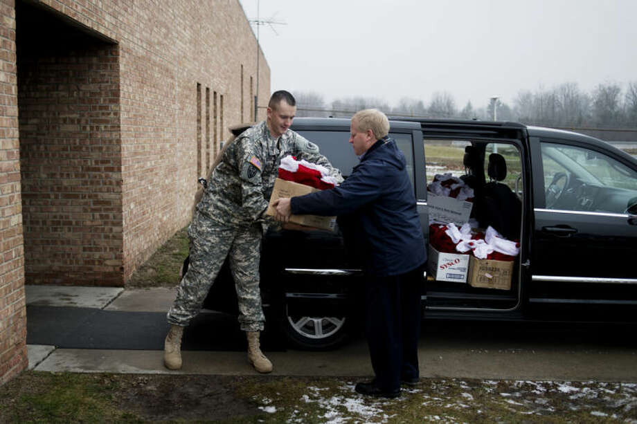 "NEIL BLAKE | nblake@mdn.netCraig Pickelman, a director at Wilson MIILER Funeral Home, passes a box of Christmas stockings to Sgt. Thomas Peeler at the National Guard Armory in Midland on Wednesday. This is the third year that the funeral home collected items from residents for Christmas stockings to give to soldiers. ""It means the world to us,"" Peeler said. Peeler returned from a deployment to Afghanistan eight months ago and said that the little things mean a lot to soldiers. Photo: Neil Blake/Midland  Daily News"