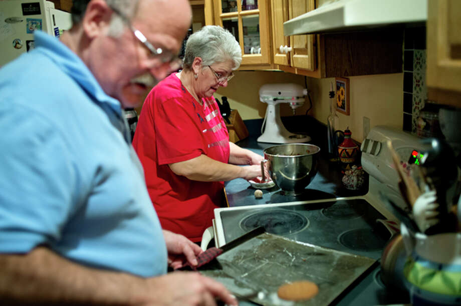 Joan Brausch and her husband Dave, make molasses cookies recently in their Midland home. Photo: Nick King/Midland  Daily News / Midland Daily News
