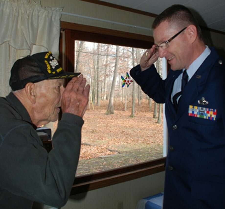 Photo providedMidMichigan Home Care volunteer, retired Air Force Master Sgt. Anthony Kirgis, salutes Chinis Bennett of Midland after honoring him with a certificate of appreciation and an American flag lapel pin from MidMichigan Home Care.
