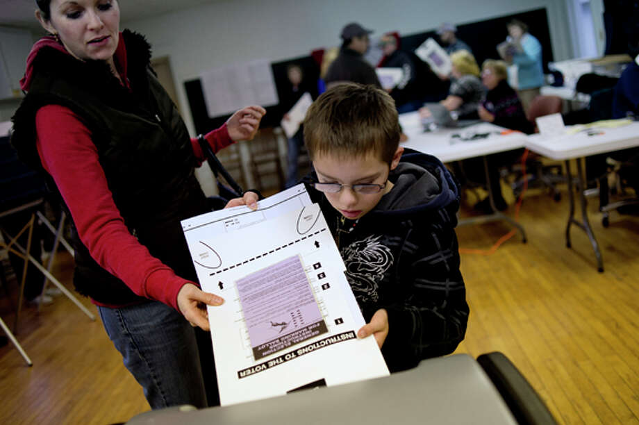 NICK KING | nking@mdn.net Jason Brown, 10, right, helps put his mother Lori's ballot into the machine after Lori voted Tuesday at the Geneva Township Hall in Coleman. Jason came along because he wanted to help his mother vote. Photo: Nick King/Midland  Daily News / Midland Daily News
