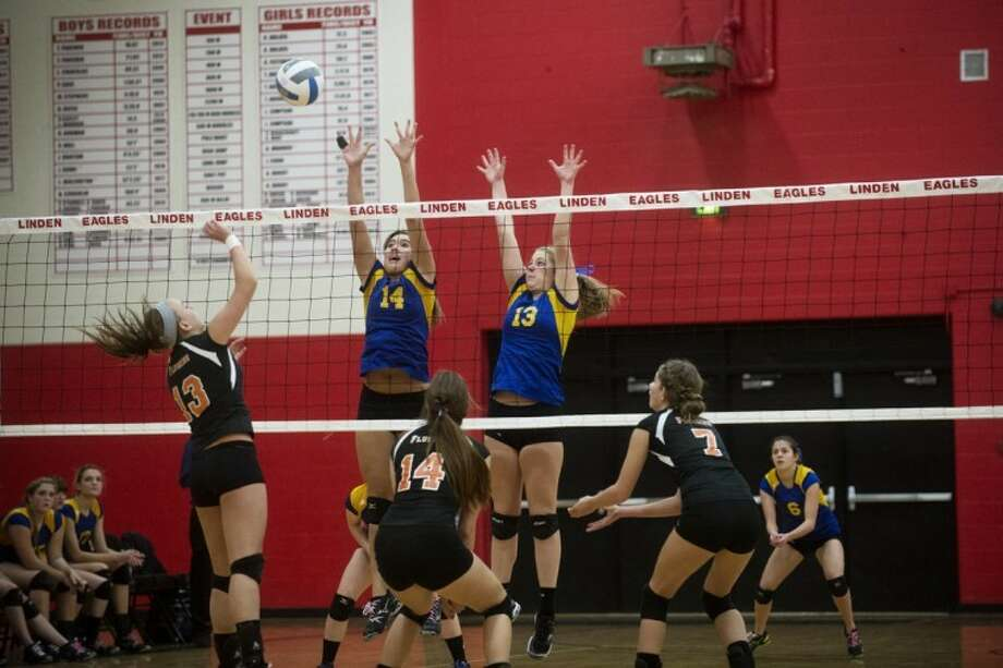 NEIL BLAKE | nblake@mdn.netMidland's Mallory Rajewski, left, and Taylor Jensen go up for a block against Flushing's Taylor Twohig (13), Bekah Kujat (14) and Sarah Wendling (7) during the regional semifinal at Linden High School on Tuesday. For more photos, click on the yellow gallery link. Photo: Neil Blake/Midland  Daily News
