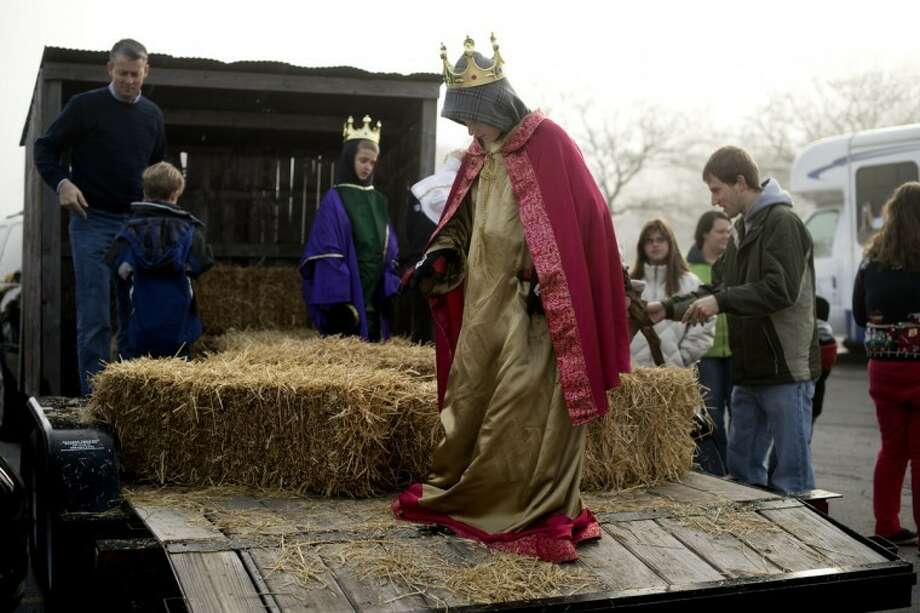 "NEIL BLAKE | nblake@mdn.netAndrew Hales, 11, smooths out his ""wise man"" robe before taking his seat on the nativity scene float from the Church of Jesus Christ of Latter Day Saints on Saturday. Photo: Neil Blake/Midland  Daily News"