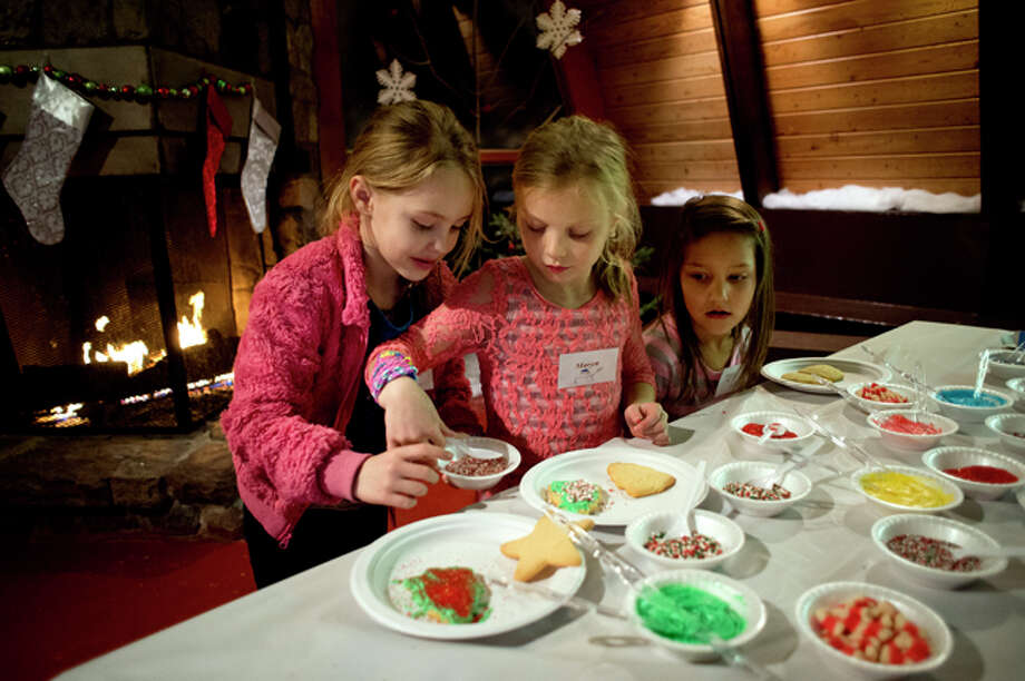 NICK KING | nking@mdn.net Seven-year-old Martina Lobo, left, and Maryn Chinyz, 7, center, work on decorating holiday cookies as Meagan Diehl, 7, right, looks on Wednesday during 'A Night at the North Pole' at the City Forest Chalet. Children participated in various holiday-related activities including Christmas crafts, cookie decorating and card making. Christmas movies were also projected on a screen for the kids to enjoy. The City Forest Chalet was decorated for the season including real pine branches collected from the forest. The annual two-day event was put on by Midland Parks and Recreation. Photo: Nick King/Midland  Daily News / Midland Daily News