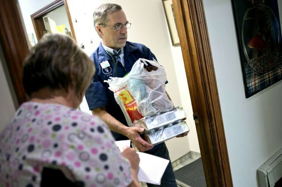 FILE — Dr. Dan White carries pet supplies to the back door of his office. Photo: Nick King/Midland  Daily News