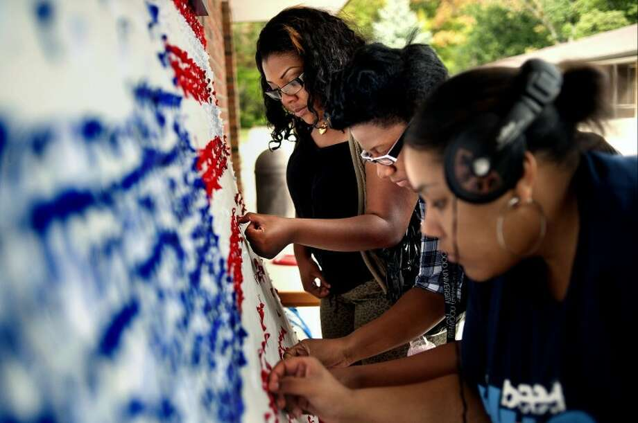 NICK KING | nking@mdn.netNorthwood students, from left Dianna Perkins, Paula Williams and Amanda Burden, place ribbons to form an American flag Thursday outside the Strosacker Library on the Northwood campus. There is one ribbon for every life lost in the 9-11 attacks. Once completed, the flag will be on display during a memorial on Sunday at 7 p.m. at the Hantz Football Field Stadium. The project was organized by the student community organization Circle K. Photo: Nick King/Midland  Daily News