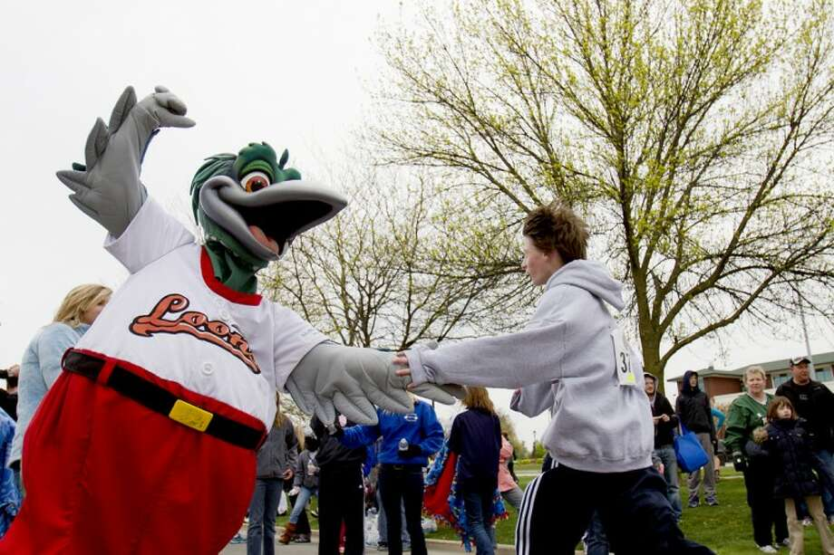 Mike Mulholland for the Daily News Great Lakes Loons mascot Lou E. Loon slaps the hand of Midland's Brennan Baldwin, 13, Saturday morning after Baldwin finished the Great Lakes Loons Race for the Pennant with a time of 27:02.