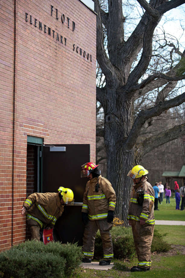 THOMAS SIMONETTI | tsimonetti@mdn.net Lee Township firefighters place a fan near a door to Floyd Elementary Wednesday afternoon after smoke was detected at the school. Students were evacuated, eventually heading back inside around 12:30 p.m.