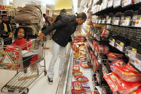 Jancy Beatriz, 3, left, looks at his mother Raquel Beatriz shop by a decimated cold cuts aisle at a Giant grocery store in Washington, on Friday, Feb. 5, 2010, hours before a massive snow storm was expected to hit the area. (AP Photo/Jacquelyn Martin)