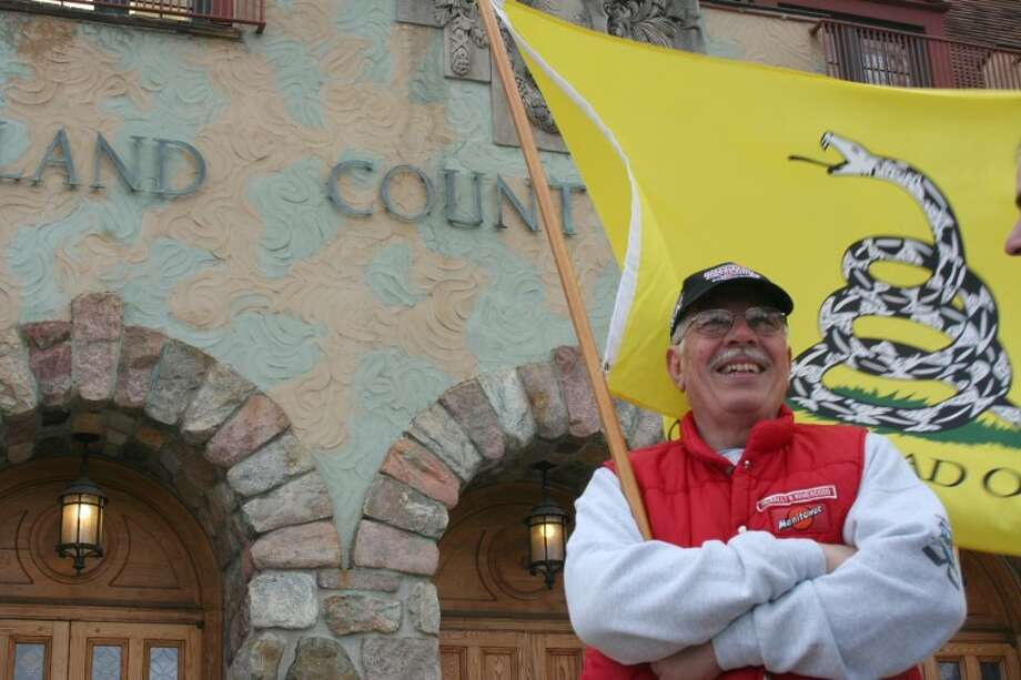 "Lisa Satayut | for the Daily NewsLee Township resident Rick Payne holds a ""Don't tread on me"" flag at the Tea Party rally in front of the Midland County Courthouse Monday evening."
