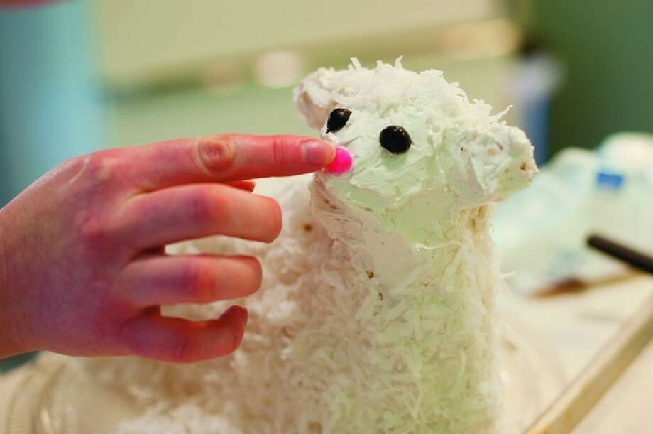NEIL BLAKE   nblake@mdn.net Ruth Clark of Midland puts on a pink jellybean nose on a lamb cake. The jellybeans and coconut complete the look of the cake. Photo: Neil Blake/Midland  Daily News