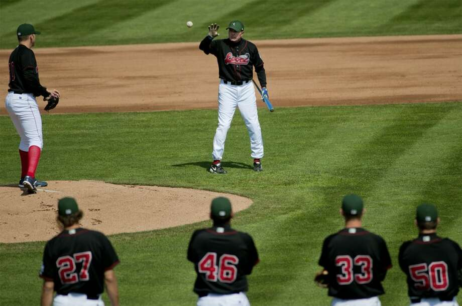 NICK KING | nking@mdn.netThe Great Lakes Loons manager John Shoemaker grabs a ball from pitcher Jarret Martin, left, as teammates look on during drills Tuesday at Dow Diamond, their first day of workouts in Midland. They start the season on Friday in Lansing.