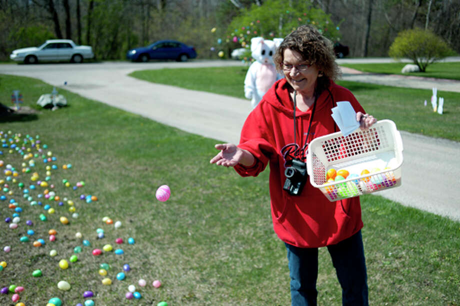 NEIL BLAKE | nblake@mdn.net Sue McMullen of Midland tosses a few more eggs onto her yard on Saturday adding to the approximately 10,000 plastic eggs scattered across the lawn. McMullen started in 2003 with 2,000 eggs and has added to them ever since. Last year, she had a friend come by dressed as the Easter Bunny to pass out candy and she continued the tradition this year. Photo: Neil Blake/Midland  Daily News / Midland Daily News