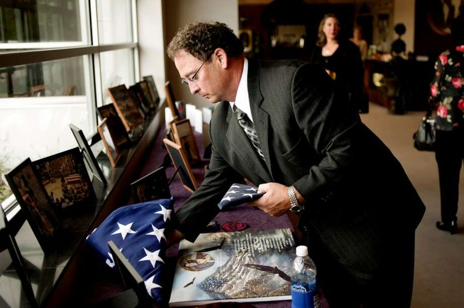 Phil Gross, father of Bryan Gross, places a folded flag among the pictures and memorabilia of his son after a memorial service for Bryan Saturday at Cleft of the Rock Church in Sanford. Converse County Deputy Bryan Gross died on July 28, 2011 while attempting to rescue a girl from a river in Wyoming where he worked. Photo: NICK KING | Nking@mdn.net
