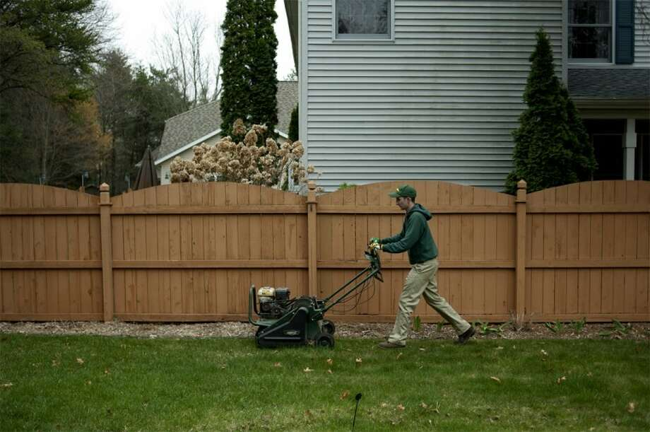 NEIL BLAKE | nblake@mdn.netTravis Vajcner of Weed Man Lawn Care aerates a lawn in Midland on Thursday. Vajcner has been working for Weed Man Lawn Care for six years.
