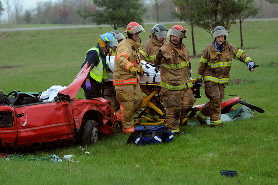 NEIL BLAKE | nblake@mdn.net Midland City Fire Department firefighters transport a man from the scene of an accident on Friday at Rockwell Drive and Bay City Road. The car hit a telephone pole breaking it in half and causing a downed wire. Photo: Neil Blake / Midland Daily News | Neil Blake