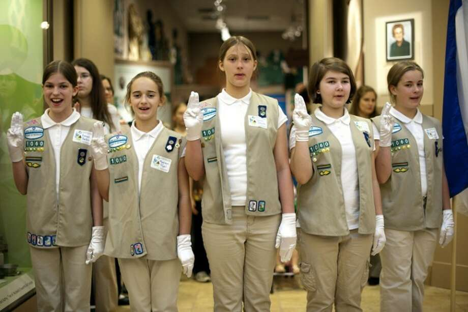 "THOMAS SIMONETTI | tsimonetti@mdn.net Left to right, Hannah Bartels, Madison Pfahl, Sarah Schulte, Kara Jobe and Rachel Crowley recite the Girl Scout Promise at the Midland Historical Society on Thursday at the opening of a new Girl Scouts exhibit titled ""100 Years and S'more: Celebrating a Century of Girl Scouting."" Photo: Thomas Simonetti"