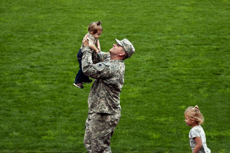 "SARA WINKLER | for the Daily News Thomas Shann of Flint picks up his daughter LilyAnn, 15 months, and holds her in the air as his other daughter Addyson, 4, follows close behind Monday evening at Dow Diamond. Shann, a soldier of the Michigan Army National Guard Company F, 23rd Brigade Support Battalion was one of many honored during a ceremony for their departure, which will be to Afghanistan on Thursday. ""Addyson knows,"" Shann said of his daughter's feelings when he leaves. ""She says I'm going to fight bad guys and save the city."" Photo: SARA WINKLER 