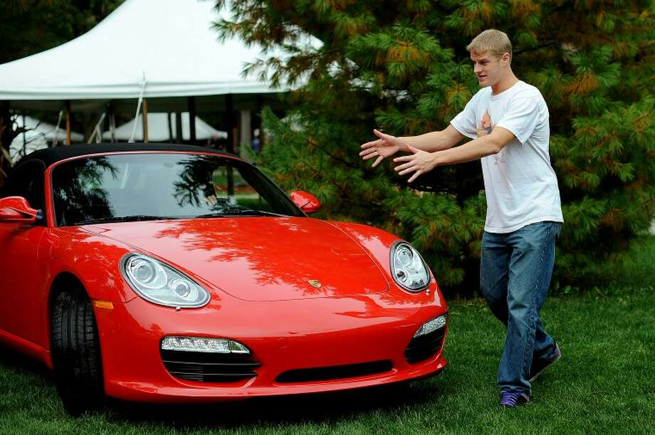 NEIL BLAKE | nblake@mdn.net Northwood senior Jake Trost directs a Porsche Boxster S onto the Team Porsche display at Northwood University on Thursday afternoon. Cars rolled in all afternoon as students prepared their displays for the Northwood's 48th annual International Auto Show which opens to the public on Friday. Photo: Neil Blake