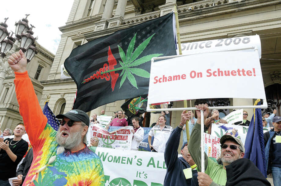 AP Photo | The State Journal | Greg DeRuiterSupporters of Michigan's medical marijuana program rally to protest recent court rulings and proposed legislative changes that would make it harder for some licensed patients to get the drug. Michigan Attorney General Bill Schuette of Midland is targeted in one of the signs. Photo: Greg DeRuiter  / The State Journal