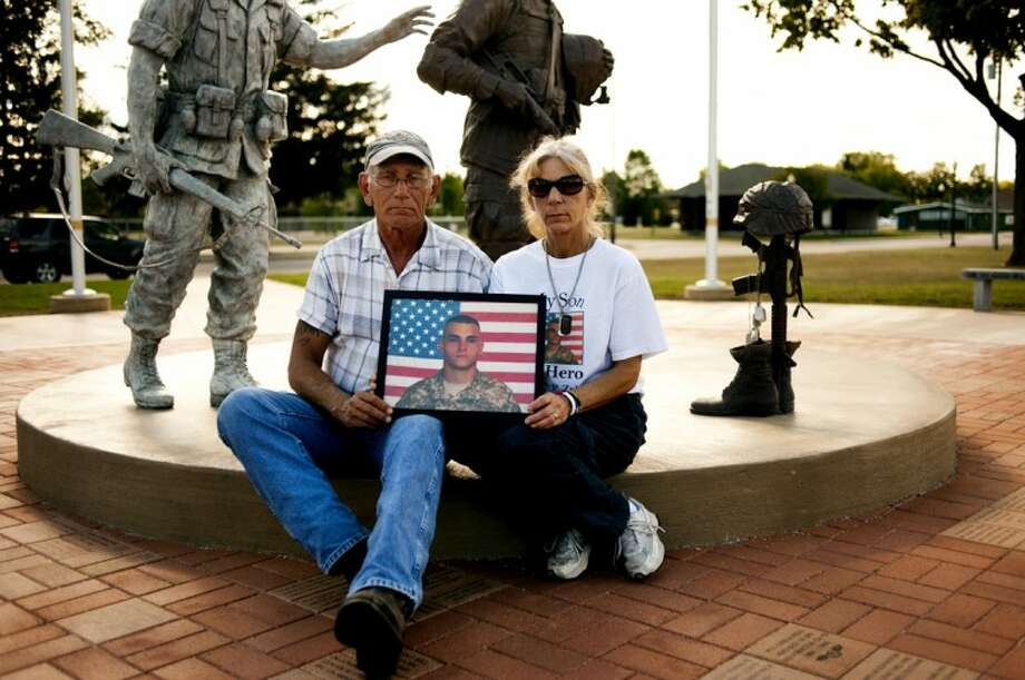 NEIL BLAKE | nblake@mdn.netRandy and Jamie Zylman, of Coleman, sit at the Coleman Veterans Memorial with a photo of their son, Casey Zylman, who was killed in action on May 25, 2007. Today Casey's dogtags hang on the battle cross with other dogtags from veterans.