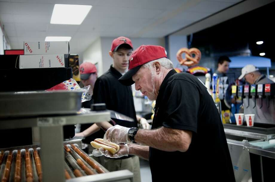 NICK KING | nking@mdn.netConcessions employee Robert Piechot prepares hot dogs for customers Tuesday during the 2012 Team Meet and Greet event at Dow Diamond. This year the Loons will have in-house food services in contrast with previous years where an outside company took care of the operation. Photo: Nick King/Midland  Daily News