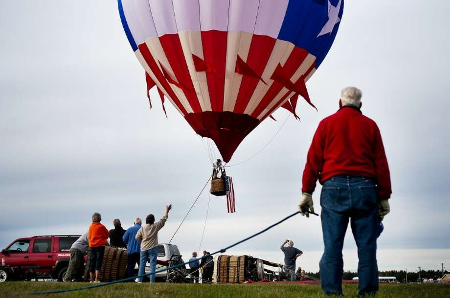 Attendees of the RE/MAX of Midland's 21st anniversary balloon festival watch as a hot air balloon takes flight with an American flag draped across the basket on Friday evening at the Midland County Fairgrounds. Photo: SEAN PROCTOR | For The Daily News