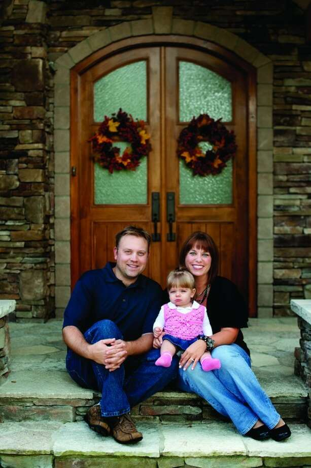NICK KING | nking@mdn.netMichael and Millie Jezior and their daughter Shelby pose outside their front door. Photo: Nick King/Midland  Daily News