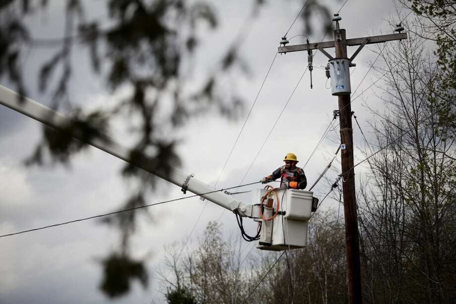 NEIL BLAKE | nblake@mdn.netConsumers Energy lineman Ray Scherf of Bay City pulls a downed power line tight on Monday on East Bombay Road in Larkin Township. The road was closed for about an hour for the repair. High winds downed trees and power lines across the county. Photo: Neil Blake/Midland  Daily News