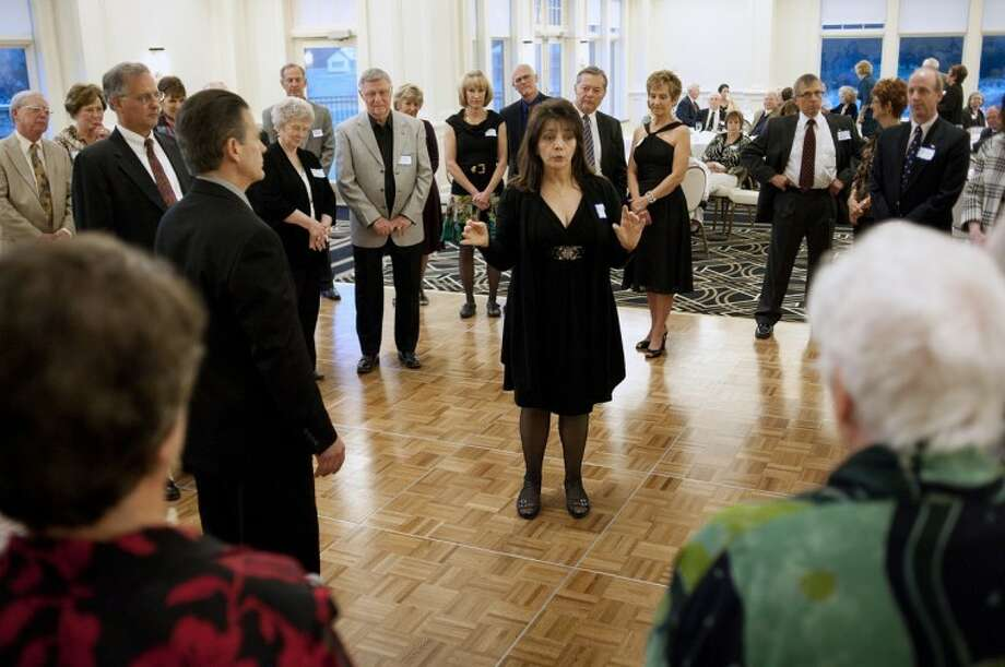 "NEIL BLAKE | nblake@mdn.netAngela Markle, foreground, of Saginaw, teaches a few steps of East Coast Swing at the ""Dancing Under the Stars"" dinner dance and lesson at the Midland Country Club on Friday. Markle said her goal for the evening was to teach the basic step and a few turns to those in attendance, many of whom were trying swing for the first time. Photo: Neil Blake/Midland  Daily News"