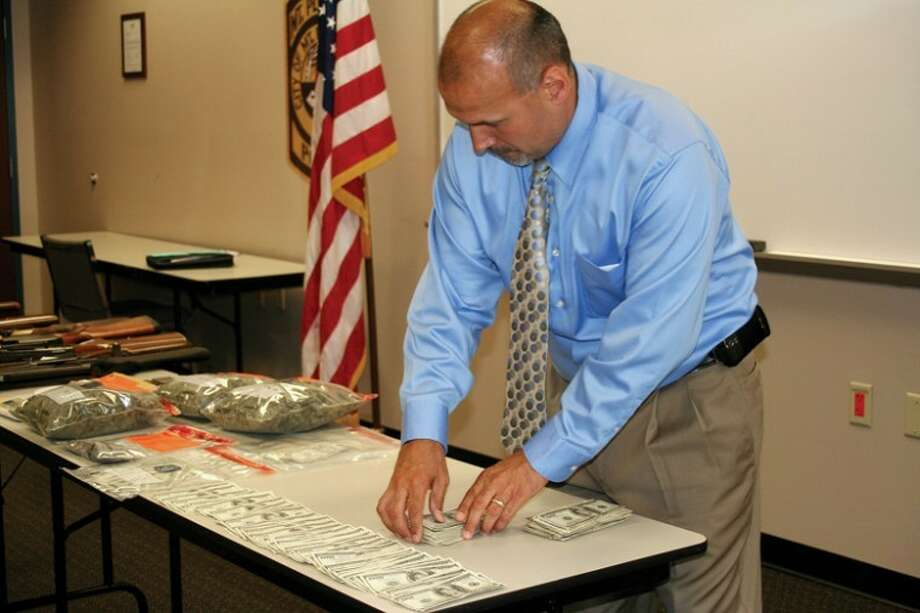 LISA SATAYUT | for the Daily NewsBayanet North Team Detective Lt. Mark Uribe handles the $28,000 seized in cash from the Clare County home.