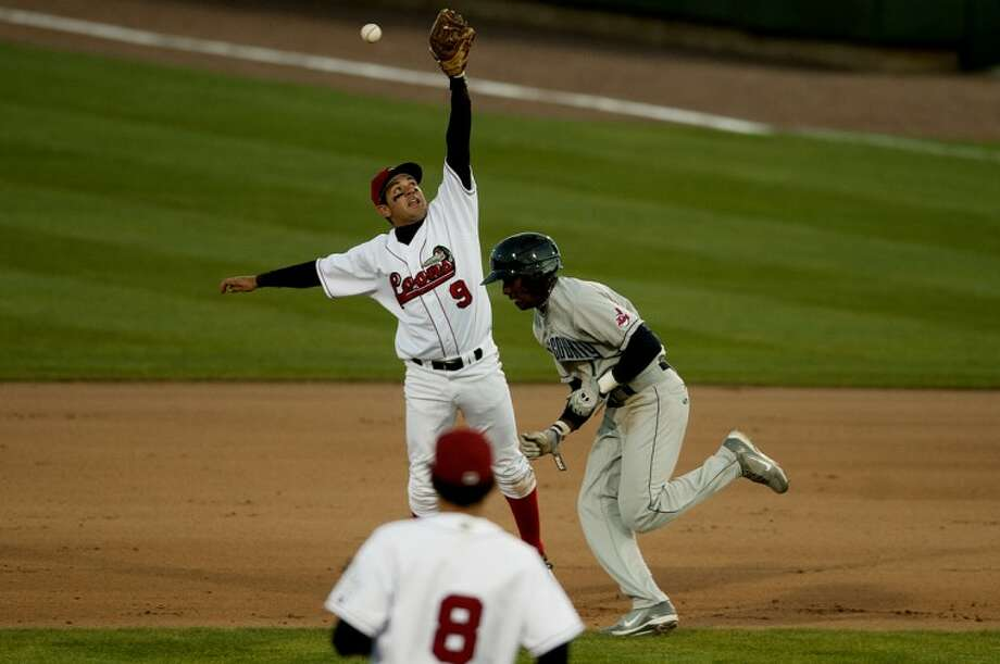 NICK KING | nking@mdn.netLoons' Jesus Arredondo, left, jumps for the ball as Captains' LeVon Washington gets caught in a pickle in the fifth inning Monday at Dow Diamond. LeVon was tagged out at second base. Loons' Justin Boudreaux (8) looks on. The Captains won 8-0. Photo: Nick King/Midland  Daily News
