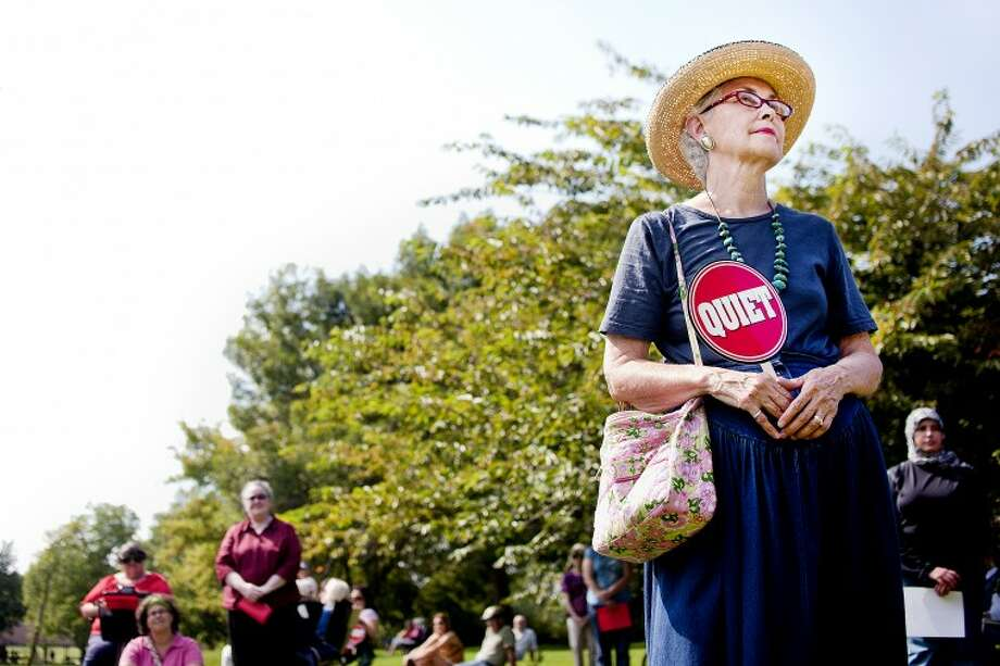 "Marge Darger of Midland, center, holds a ""QUIET"" sign as she stands in front of mothers, grandmothers, daughters and granddaughters who came to support her and the Helen M. Casey Center for nonviolence by silently gathering Sunday afternoon along the Pere Marquette Rail-Trail next to the Tridge. Darger, along with Jeanne Lound Schaller, organized the peace gathering with influence from the anniversary of the Sept. 11 terrorist attacks, which coincidentally coincided with 'Grandparents Day' this year. ""I think we have something in our world where war is no longer the answer,"" Darger said. ""You really do have to start someplace."" Photo: SARA WINKLER 
