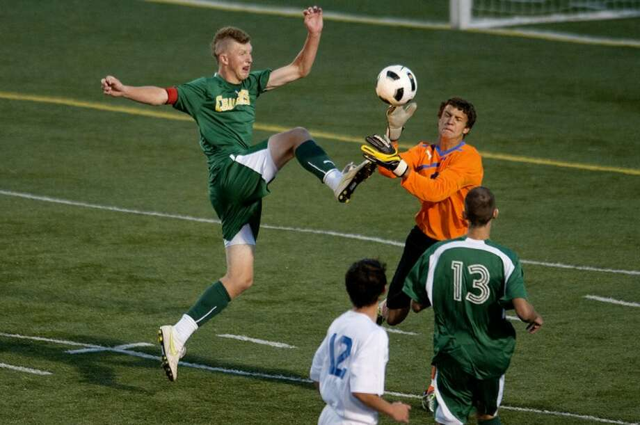 NICK KING   nking@mdn.netDow's Connor Baak, left, kicks the ball as Midland's goalkeeper Ryan Sugnut defends in the first half. Photo: Nick King/Midland  Daily News