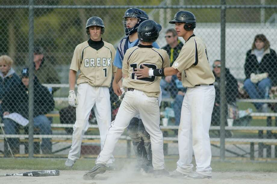 NICK KING | nking@mdn.netBullock Creek's Josh Bailey, right, and Jacob Fleming celebrate their runs in the sixth inning Thursday at Bullock Creek High School. In the background at left, Bullock Creek's Jacob Dean and Meridian's Zac Arthur look on. Bullock Creek won game one of the doubleheader 5-3. Photo: Nick King/Midland  Daily News
