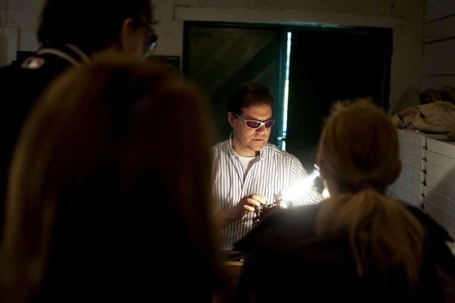 LIBBY MARCH | for the Daily NewsTim Drier uses a torch to heat glass and form a butterfly at the barn at Dow Gardens. Drier gave demos and made butterflies for customers as they watched. His glasses, made of Didymium, allowed him to filter out the yellow color of sodium flare in the flame so it didn't obscure his ability to work with the glass. Photo: Libby March