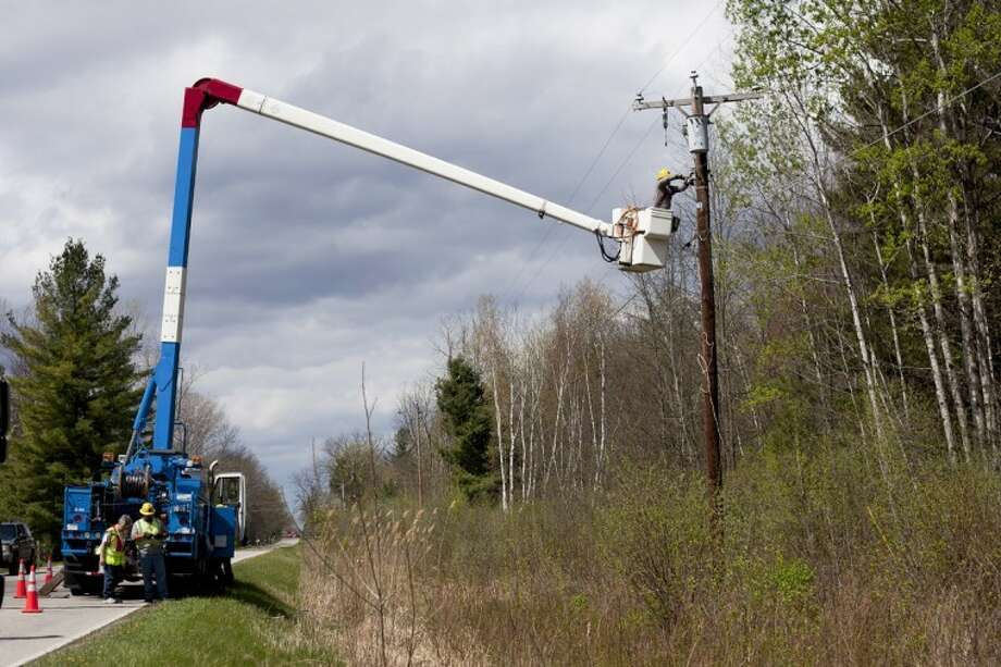 NEIL BLAKE   nblake@mdn.netA Consumers Energy crew works on a downed power line on East Bombay Road on Monday. High winds swept through the area, damaging trees and power lines throughout Midland County. Photo: Neil Blake/Midland  Daily News