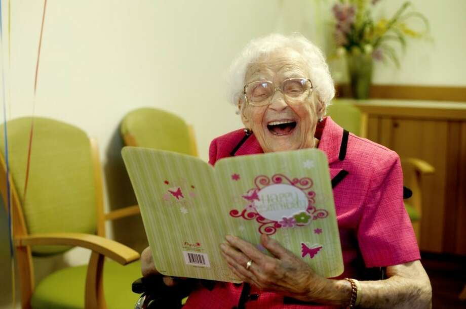 NEIL BLAKE   nblake@mdn.net Violet Smith laughs as she reads a birthday card celebrating her 110th birthday at the King's Daughters Home in Midland. Smith was born on April 7, 1902, and grew up in Saginaw. Smith is Midland county's oldest resident. Photo: Neil Blake/Midland  Daily News