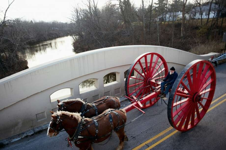 Moses Yoder of Clare drives a team of Belgians pulling a Michigan big wheel to the Sanford Centennial Museum on Friday morning along 7 Mile Road in Sanford. The wheel is a full size replica of the ones used for logging in the late 19th century and early 20th century. The Sanford big wheel was built by a team of volunteers spearheaded by John Billingsley of Sanford. Photo: NEIL BLAKE | Nblake@mdn.net