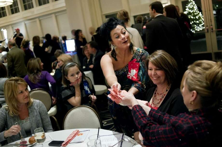 Vicky Jezewski, left, sells raffle tickets to Sue Houlihan, from First American Title, center, and Nancy Billingsley, with the Bay County Realtor Association, right, Thursday during the Holiday Wishes Charity Gala at the Midland County Club. Raffle tickets were sold in order to raffle off the over-125 items donated for the charity event. The charity event benefits the United Way, Midland Area Homes and the Railway Family Center. Photo: NICK KING   Nking@mdn.net