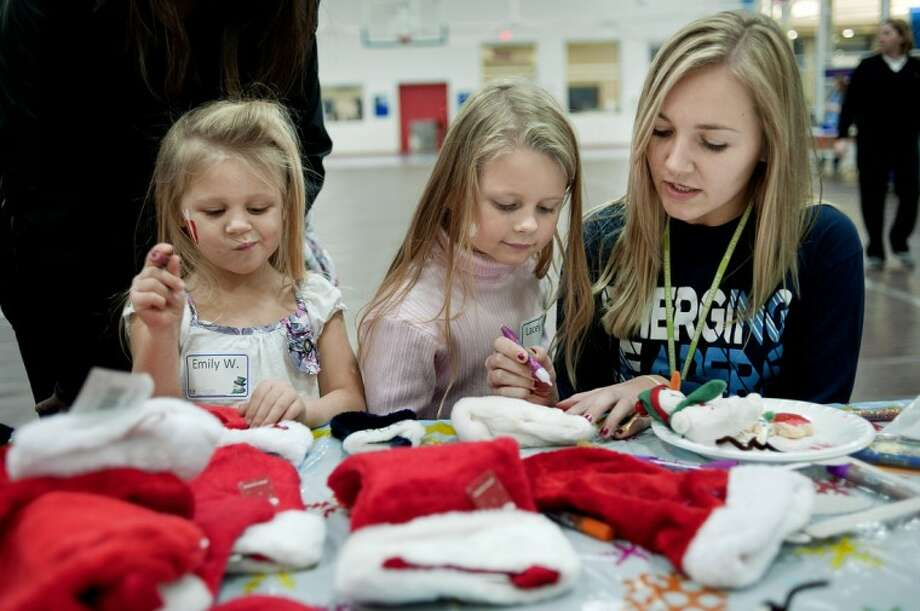 From left, sisters Emily Waite, 4, and Lacey Waite, 5, decorate stockings with Northwood students freshman Julie Johnson, right, and senior Stephanie Titus (not pictured) Wednesday in the gym at the Hach Student Life Center on the Northwood campus. Northwood University's Student Government Association and Emerging Leaders hosted the annual Salvation Army Christmas Party for 27 local children. Children were paired up with Northwood students. Each pair ate dinner, enjoyed caroling, gift sharing, crafts and games provided by various Northwood student organizations. Photo: NICK KING   Nking@mdn.net