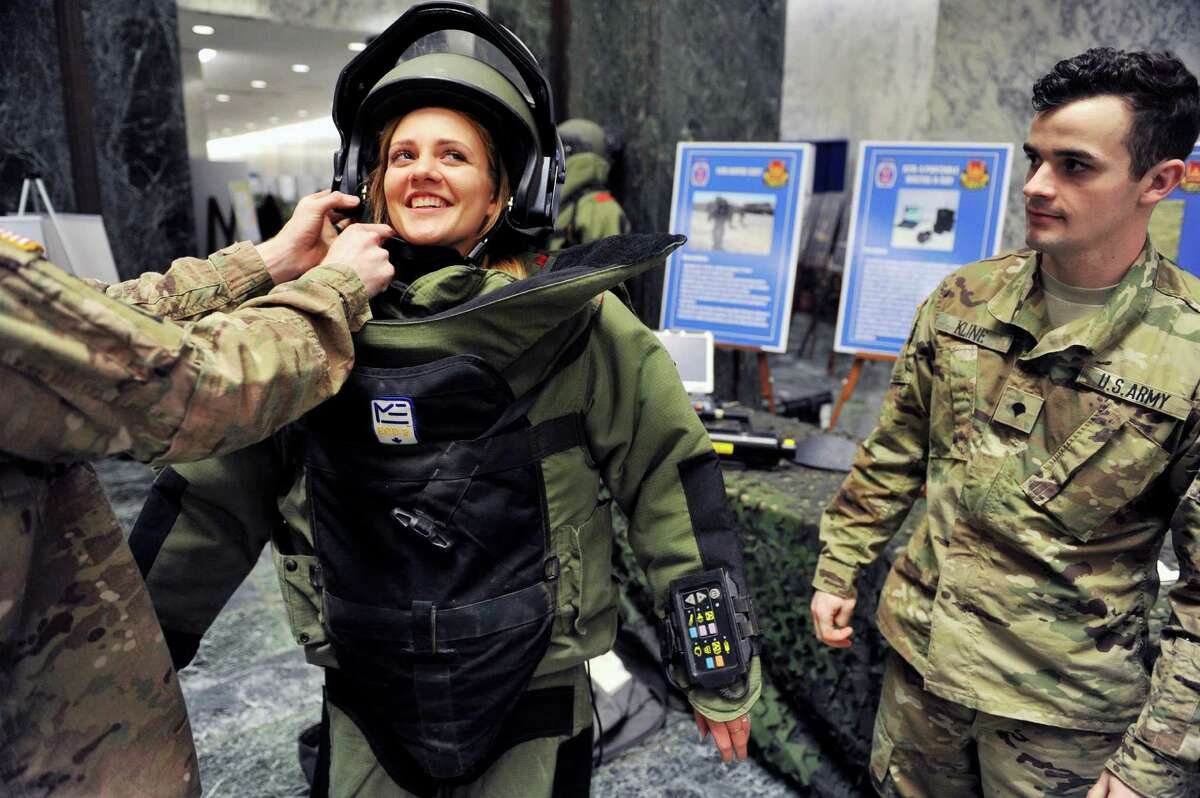 Members of the 760th Ordinance Company out of Fort Drum, Cpl. Dillon Thiel, left, and Spc. Eric Kline, right, help Nicole Danyi, 17, from Baldwin High School into a bomb suit as soldiers from Fort Drum took part in Fort Drum Day at the Legislative Office Building on Tuesday, March 22, 2016, in Albany, N.Y. (Paul Buckowski / Times Union)