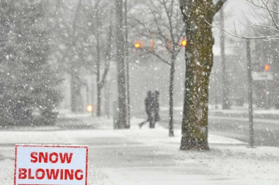 AP Photo | Traverse City Record | Vanessa McCrayPeople walk through falling snow in Traverse City on Sunday. A winter storm in western and northern Michigan was expected to bring 12 to 18 inches of snow by late Monday, as well as winds gusting to 55 miles per hour Photo: Vanessa McCray