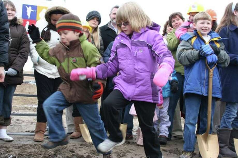 Sara Araway, 6, and Eli Buccilli, 5, jump over mini mounds of mud before the groundbreaking ceremony for the soon-to-be Mt. Pleasant Discovery Museum Friday afternoon. The children's museum is described as an interactive hands-on learning experience with exhibits featuring science, music, art, literacy and gross motor skills. Photo: LISA SATAYUT | For The Daily News
