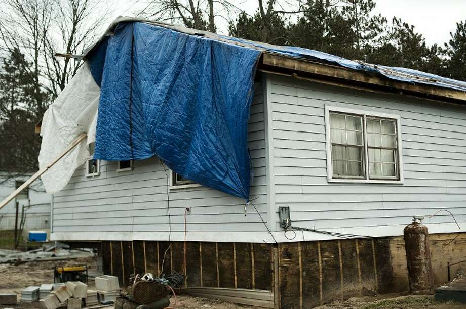 Lyle Blimka's home in Sanford is covered in tarps to keep out the elements. The mobile home was moved to the property in September and has been without a roof ever since. Photo: NEIL BLAKE | Nblake@mdn.net
