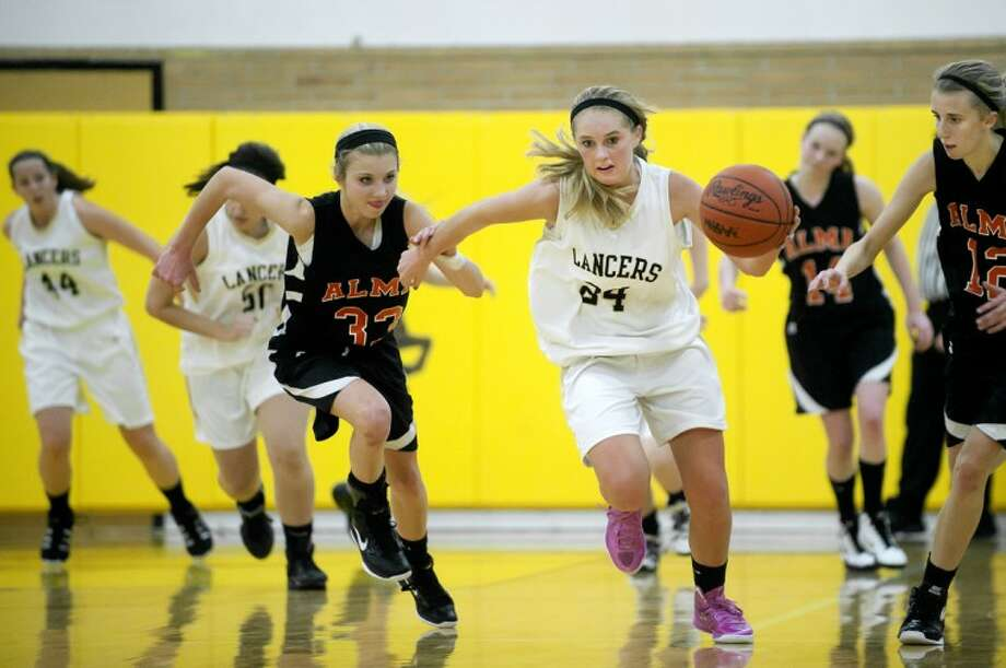 Bullock Creek's Ellie Juengel, center, leads a fast break after a steal as Alma's Madison Seeley, left, and Sam Messer close in during the second period Tuesday at Bullock Creek High School. Photo: NICK KING | Nking@mdn.net