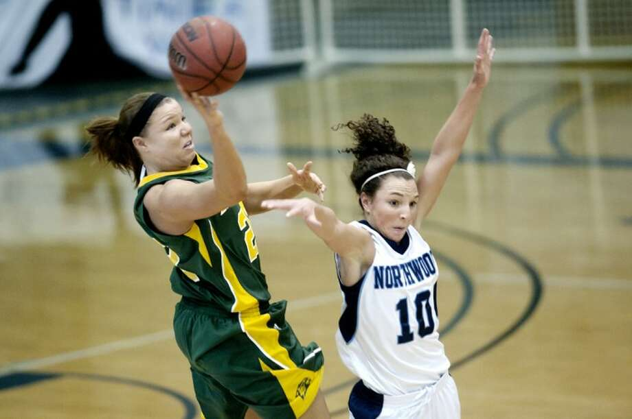 NICK KING | nking@mdn.netNorthwood's Sara Spring, right, defends as Northern Michigan University's Chelsea Lyons shoots before the first-half buzzer sounds Saturday at the Bennett Sports Center. Photo: Nick King/Midland  Daily News