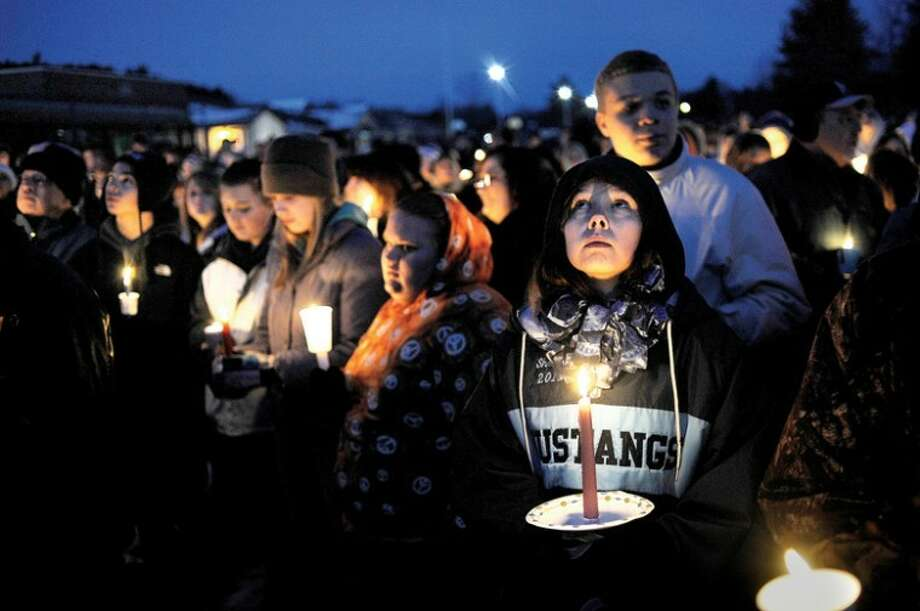 NICK KING | nking@mdn.netMeridian High School junior Shelby Owens watches a balloon rise into the sky after it was released in honor of Bob Cole during a candlelight vigil for the missing Meridian track coach. Photo: Nick King