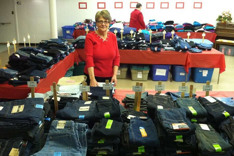 Lori Jackson, co-chair of King's Daughters Christmas Closet, is shown with some of the clothes that were purchased for the roughly 1,800 children from 920 families that were served by the King's Daughters program this year, which has been serving Midland County children in preschool through 12th grade since 1961. In the background is Christmas Closet co-chair Ann O'Connell. Photo: Photo Provided