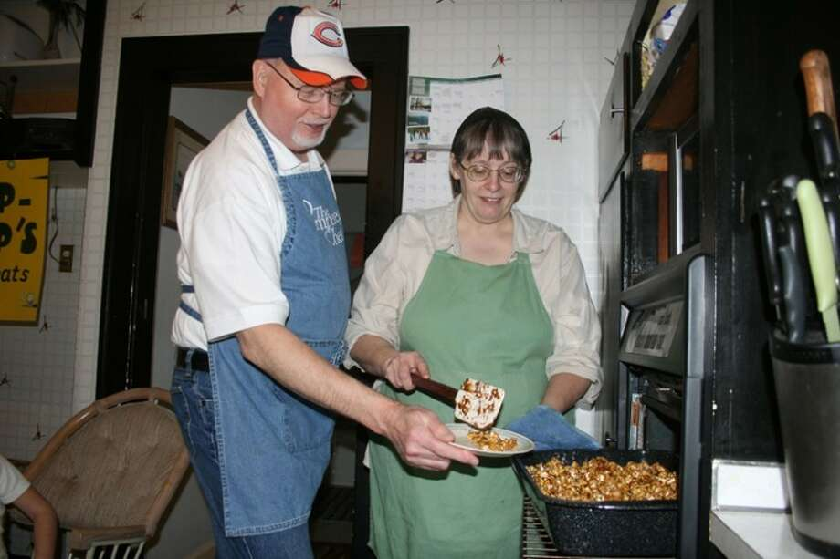 Tracy Burton | for the Daily NewsPatty McFarland offers her husband and business partner, Gene, a quick sample of caramel popcorn that was just minutes away from being done.